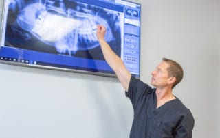 Dr. Davis pointing at an x-ray of a mouth